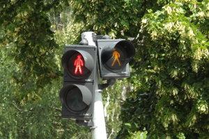 Vodičov upozorňuje na chodcov blikajúci oranžový panáčik.