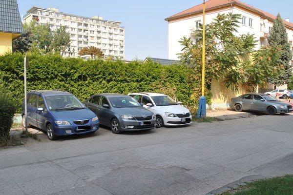 Autá parkujú zadnými časťami na chodníku a prednými na bývalom trávniku.