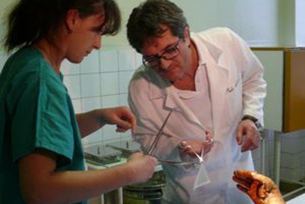 Primár oddelenia Ladislav Korec ošetruje ruku pacienta počas preväzu. Pred mesiacom o ňu takmer prišiel.