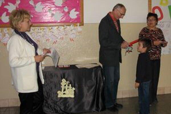 Riaditeľ školy Ľubomír Záleský povyšuje jedného z prváčikov na školáka.
