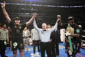 Rozhodca po zápase dvihol ruky nad hlavu obom boxerom.