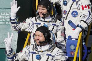 Účastníci Expedície 58 Anne McClainová, v strede, Оleg Kononenko, dole, a David Saint Jacques mávajú pred nástupom do rakety Sojuz.