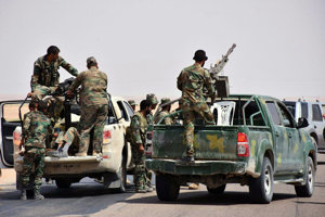 Sýrski vojaci a provládni ostreľovači stoja na pickupoch s raketometmi vo východnej sýrskej provincii Dajr az-Zaur.