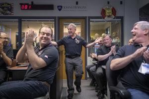 Astronóm Alan Stern (uprostred) sa raduje s ostatnými členmi tímu po prijatí signálu zo sondy New Horizons.