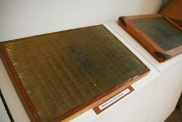 Na fotografii sú sitá na ručné papiere. Ručné papiere mali priesvitky, vodoznaky. Priesvitky zo 17. storočia z najstaršej liptovskej papierne znázorňujú dve skrížené kosy alebo banícke čakany, nad ktorými bol trojlístok, prebrali motív z erbu Partizánskej