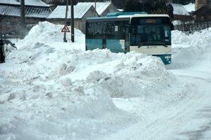 Autobus prechádza cez snehové záveje na ceste pred obcou Ladmovce.