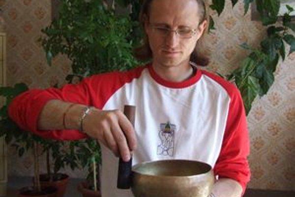 Rozozvučaná tibetská misa naplnená vodou pripomína fontánu. Drobné kvapky vody vystrekujú z misy.