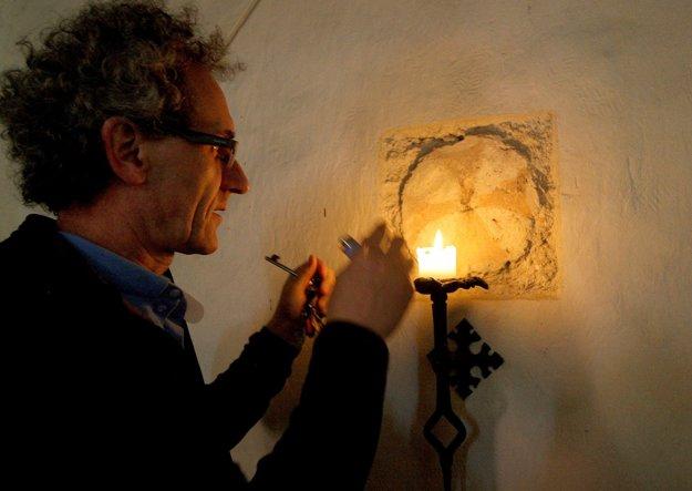 Farár Dušan Mesík zapaľuje sviecu pri historicky veľmi hodnotnom konsekračnom kríži.