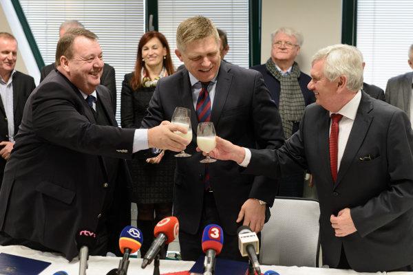 Zástupca spoločnosti Midia Agro Norman Patrick Turner, premiér Robert Fico a minister pôdohospodárstva Ľubomír Jahnátek si pripíjajú mliekom po podpise zmluvy.