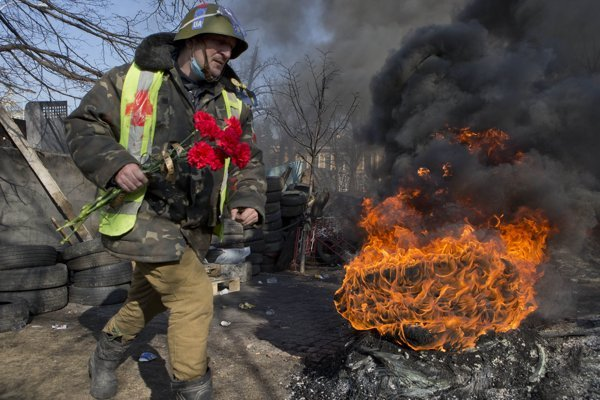 21. február 2014. Protivládny protestujúci nesie kvety na miesto, kde deň pred tým zabili jeho kamarátov.