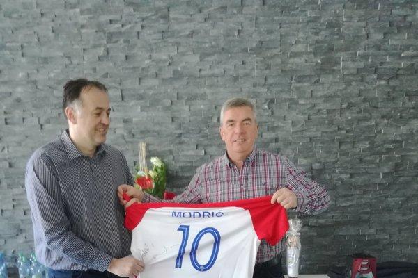 Tréner Goluža odovzdáva majiteľovi Chmeliarovi dres Modriča.