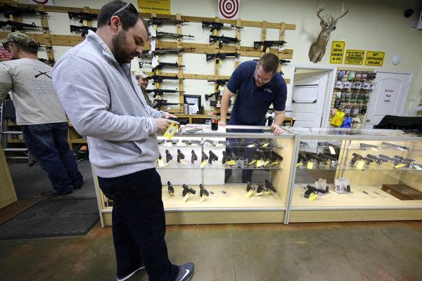Zákazník David Foley (v strede) drží zbraň v obchode špecializujúcom sa na predaj zbraní v meste Spring, v americkom štáte Texas.