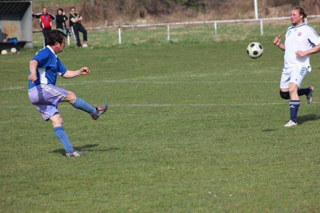 Peter Ďuriš (v modrom) odkopáva loptu do bezpečia.