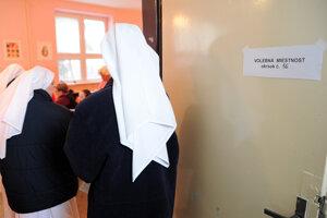 Rehoľníčky Kongregácie sestier premonštrátok vchádzajú do volebnej miestnosti počas volieb v Nitre.