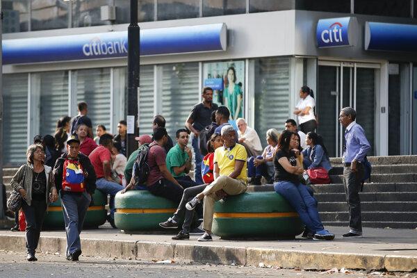 Obyvatelia Caracasu čakajú red zavretou bankou.