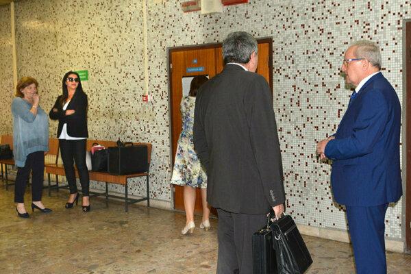 Vľavo Mojsejová s advokátkou, vpravo exekútor s advokátom.