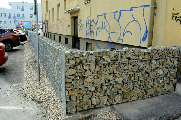 Obyvatelia sa sťažujú na múrik pre ich obmedzovanie aj preto, že stojí nelegálne na mestskom pozemku.