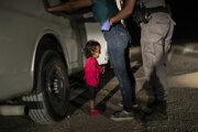 """Víťazná fotografia World Press Photo od Johna Moora. Samotný Moore, pracujúci pre agentúru Getty Images, poznamenal, že táto scéna na hraniciach """"sa dotkla sŕdc mnohých ľudí tak ako aj môjho""""."""