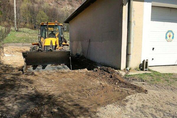 Stavba prístavby garáže k zbrojnici.