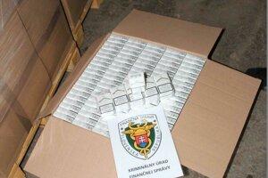 Pri prehliadke viacerých pozemkov našli kriminalisti FS viacero škatúľ, plných cigariet.