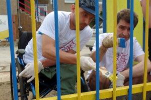 Dobrovoľníci natierajú plot v Centre voľného času Nižná Úvrať 26 v Košiciach.
