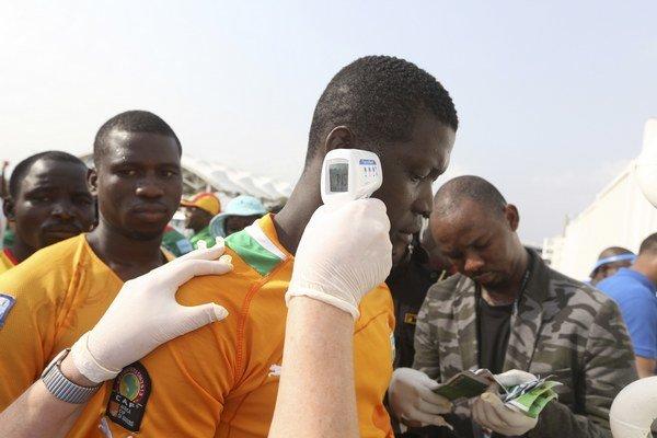 Zdravotník meria teplotu na detekciu prítomnosti vírusu ebola.