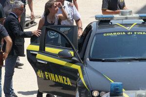 Carola Racketeová odchádza v sprievode finančnej polície zo sicílskeho prístavu Porto Empedocle.