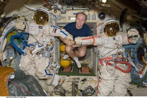 Kozmonaut Oleg Kotov pózuje na ISS s dvomi ruskými skafandrami Orlan.