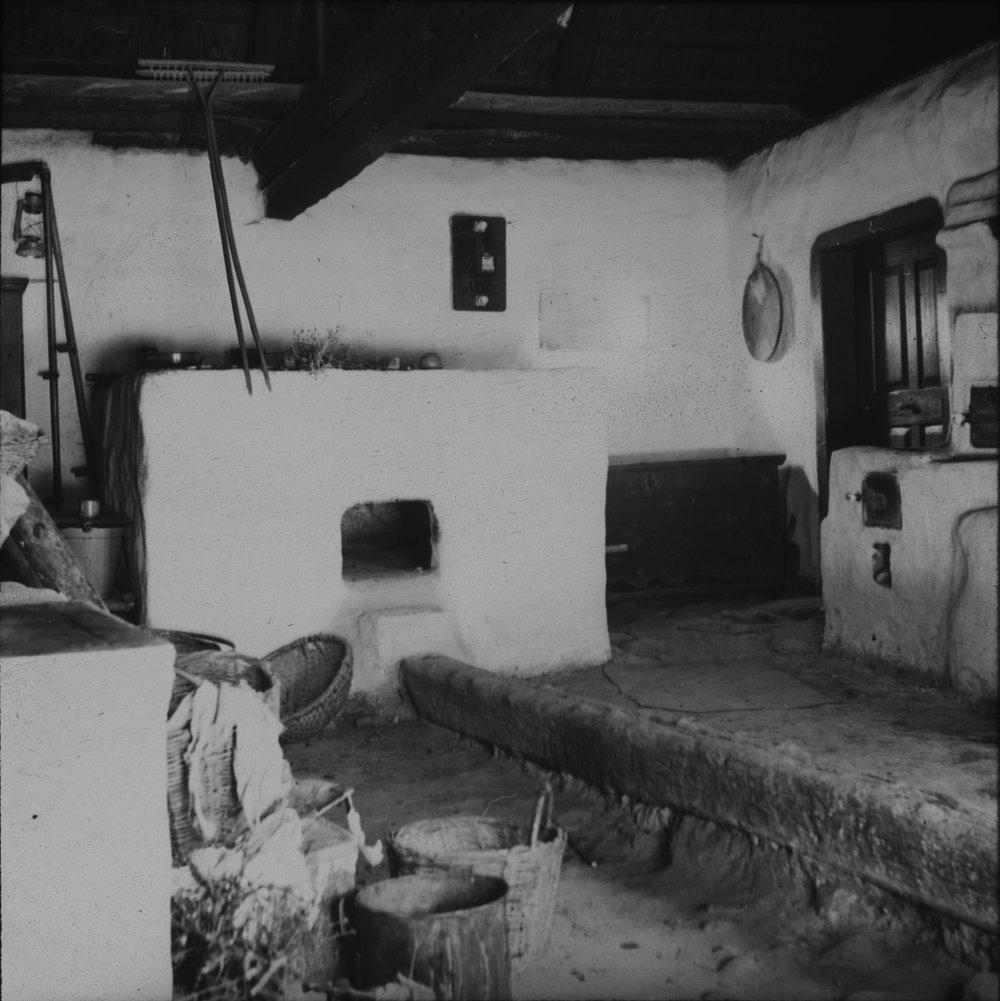 Interiér izby s pecou v archaickom ľudovom obydlí vo Vysokých Tatrách. 30. roky 20. storočia.