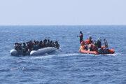 Ilustračné foto - migranti na rafte blízko Líbye a pomoc z lode NGO.