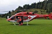 Záchranári nakladajú obarené dieťa do vrtuľníka.