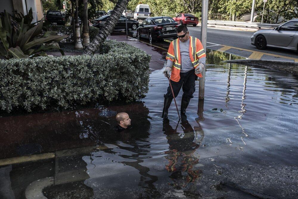 Miami. Obrovský príliv na Miami Beach. Voda preniká do ulíc cez slabo udržiavanú hrádzu v Indian Creek a cez odvodňovací systém. Pracovníci kontrolujú, či odvodňovací systém nie je zablokovaný.