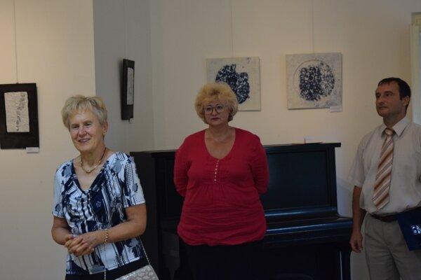 Vernisáž výstavy Vrstvy zeme. Kurátorkou výstavy je Kinga Szabóová (Vľavo). Tibor Pálinkas (vpravo) predstavil tvorbu Adrieny Kutakovej (v strede)