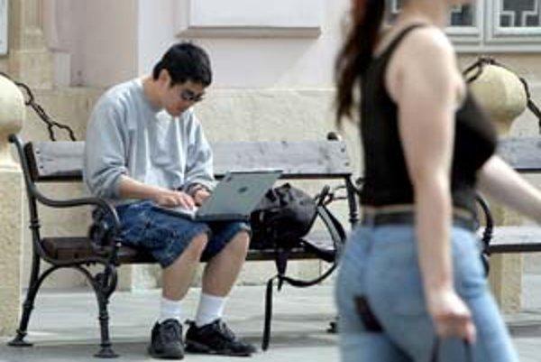Turista surfuje po internete na bratislavskom námestí. Náhodných okoloidúcich bezplatný internet teší, obyvatelia ho však vo svete využívajú veľmi málo.
