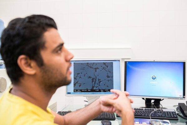 Doktorand Ahmed Ibrahim skúma mikroskopom štruktúru. Má na starosti prípravu nových špeciálnych materiálov pre zubné implantáty.