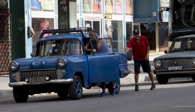 Muž tlačí vozidlo na benzínovú pumpu v Havane.