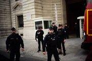 Policajti hliadkujú pred budovou, kde sa útok odohral.
