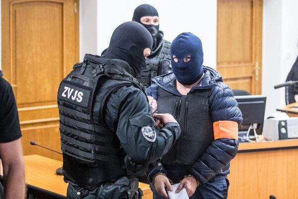 Polícia Zoltána Andruskóa chráni aj pred medializáciou. Takto mu umožnila ukryť svoju tvár pred novinármi počas pojednávania na Okresnom súde Bratislava V., kde je Andruskó obžalovaný za daňový podvod: Andruskó je v modrej kukle s oranžovou páskou na ramene.
