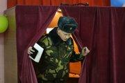Bieloruský vojak vychádza z plenty s hlasovacím lístkom počas hlasovania v parlamentných voľbách vo volebnej miestnosti v Minsku 17. novembra 2019.