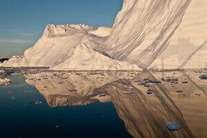 Polnočné Slnko vrhá zlatú žiaru na ľadovec a jeho odraz v zálive Disko. Grónsko ročne stráca najviac ľadu pri telení takýchto ľadovcov. Telenie je odlamovanie obrovských ľadových blokov.