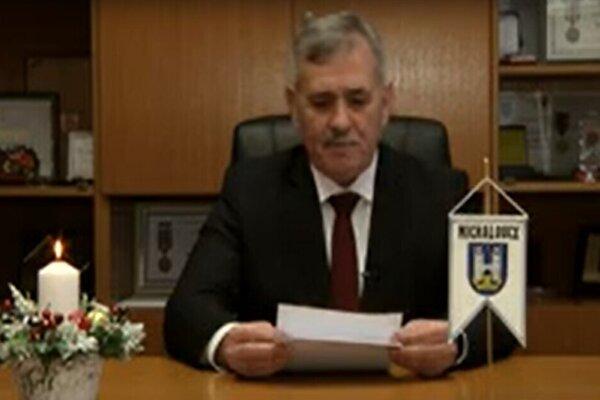 Viliam Zahorčák v novoročnom príhovore. Prečítal ho z papiera, na stole stála vlajočka s erbom mesta. Primátor spomenul aj svoju kandidatúru do parlamentu.
