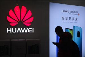 Na archívnej snímke muž si pozerá smartfón pred obchodom Huawei v Pekingu.