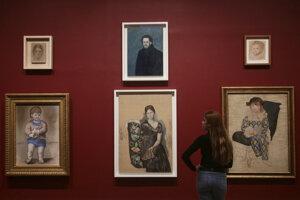 Žena stojí pred rôznymi portrétmi od Pabla Picassa  na výstave Picasso 1932 - Láska, Sláva, Tragédia v galérii britského národného múzea moderného umenia Tate Modern v Londýne 6. marca 2018.
