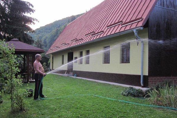 František Oršula polieva trávnik a záhradu pred chatou vodou z potoka.