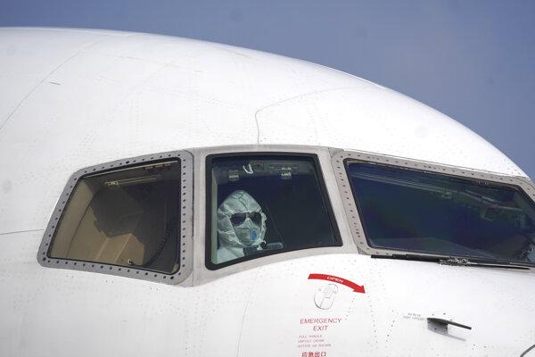 Pilot v ochrannom obleku sedí v lietadle na letisku v čínskom meste Wu-chan.