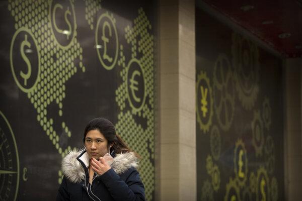 Žena kráča okolo banky so symbolmi svetových mien v Pekingu.