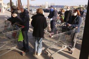 Ľudia v talianskom meste Casalpusterlengo čakajú pred obchodom. Mesto izolovali, ľudia z neho nemôžu pre šíriaci sa koronavírus odísť.