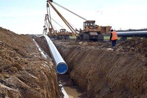 Pokládka oceľového potrubia do vykopanej ryhy na výstavbe prepojovacieho plynovodu medzi Slovenskom a Poľskom pri obci Krišovská Liesková v okrese Michalovce.