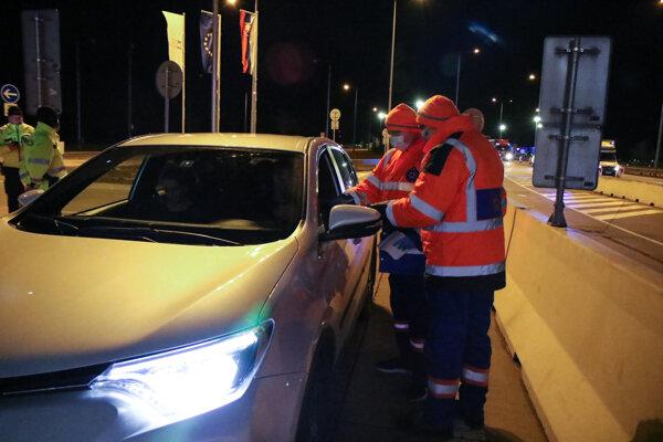 Dobrovoľníci Civilnej ochrany Slovenskej republiky rozdávajú informačné materiály vodičom cestujúcim autami z Rakúska v rámci prevencie a ochrany pred šíriacim sa koronavírusom, na hraničnom priechode Bratislava - Jarovce 28. februára 2020.