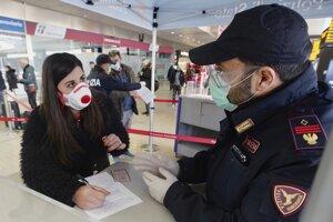 Cestujúca s ochranným rúškom vyplňuje formulár na kontrolnom stanovišti talianskej polície na železničnej stanici Termini v Ríme.